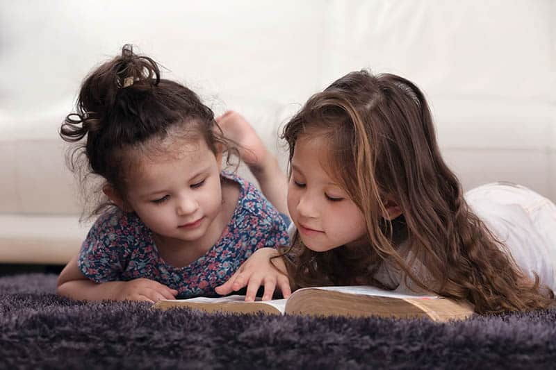 Two sisters reading the Bible. Dwell in the Word to combat the enemy's lies