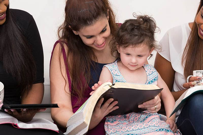 Christian woman modeling Bible study for her young daughter