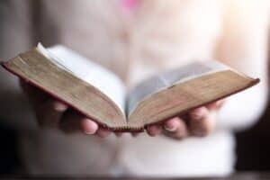 Who's approval are you working for? Featured Image of woman holding an open Bible in her hands.