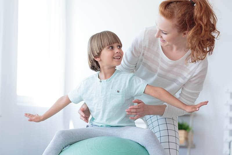 Christian mom playing with her son on an exercise ball | Guide to dealing with unexpected change