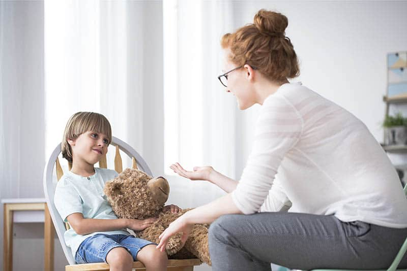 Mother talking to polite son hugging teddy bear