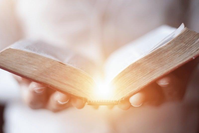 Christian woman's hands holding an open Bible
