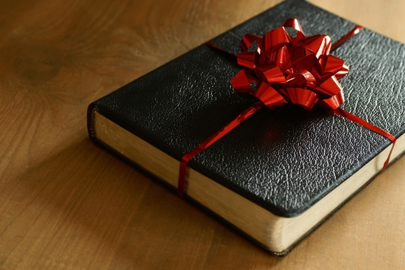 Bible wrapped in a bow to illustrate the importance of learning to value the gift of Scripture