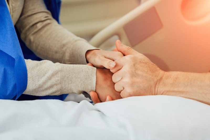 woman holding father's hand in hospital | how NOT to be passive about your purpose