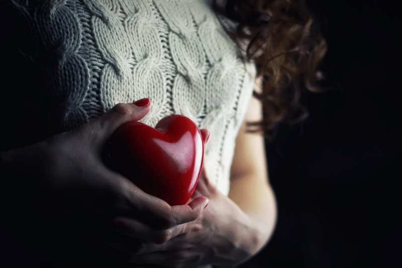 woman holding plastic heart  | how NOT to be passive about your purpose