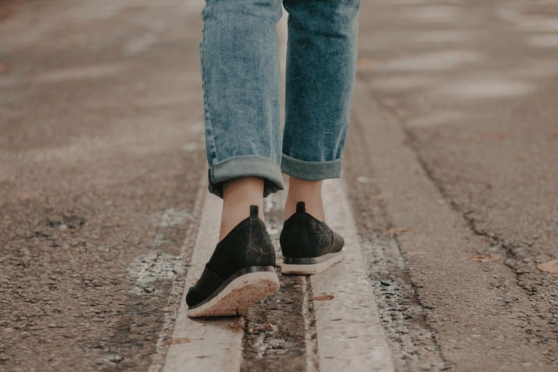 woman's feet walking down the center of the road