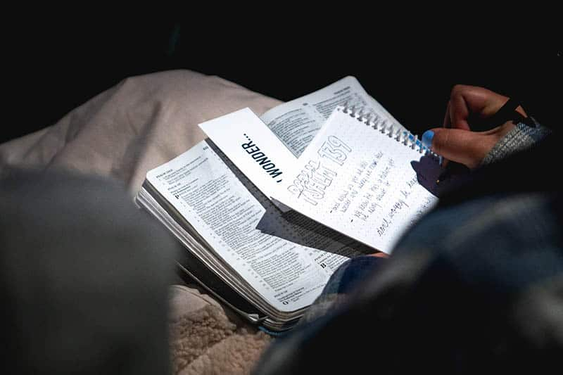 Christian woman reading her Bible with a notebook in hand | Engage with God's Word