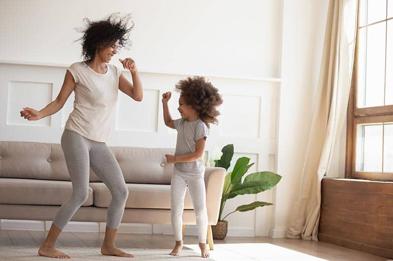 African daughter and mother dancing in modern cozy sunny living room   biblical wisdom for joyful homemaking