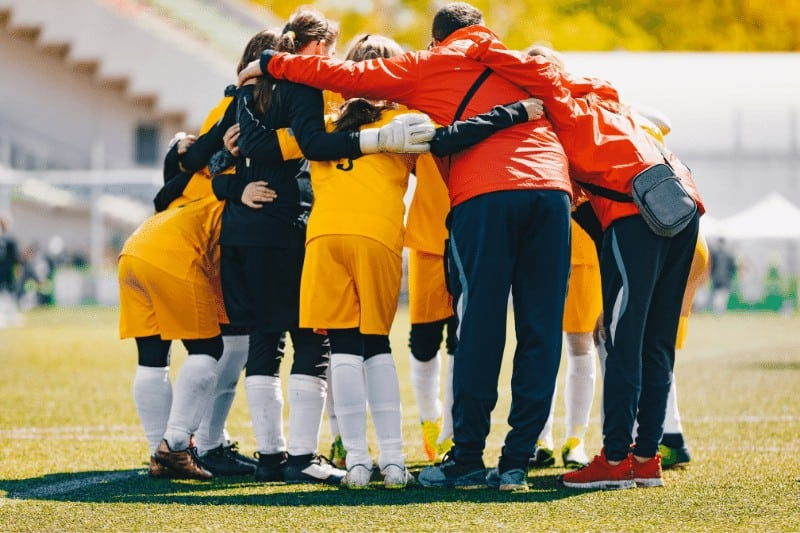 soccer team gathered in a huddle on the field | How to be Intentional Leaders