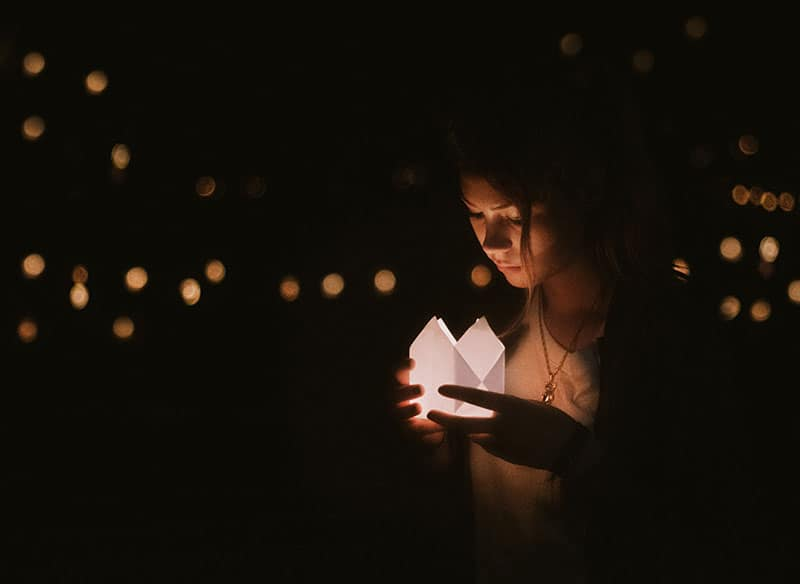 woman looking at paper lantern with twinkle lights in the background | God sees