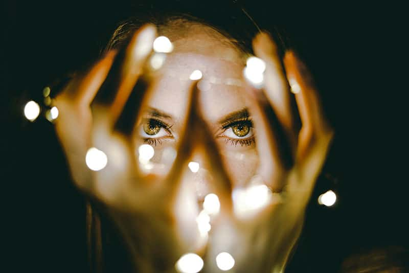 woman's eyes in the dark with twinkkle lights | God sees