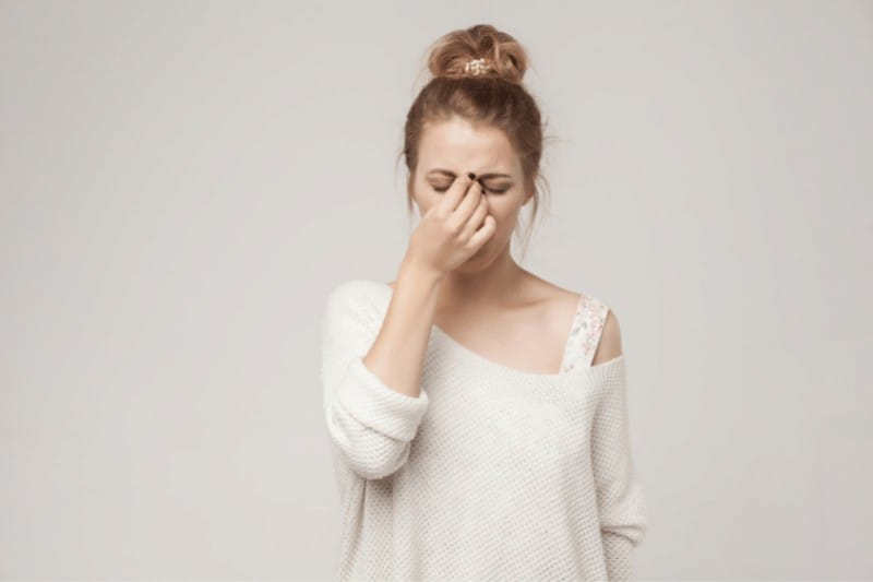 Stressed out woman pinching between her eyes  | 6 Reasons to Choose to Trust God During Seasons of Pain