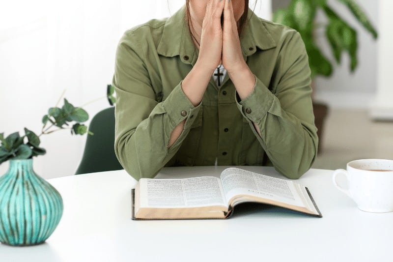 woman praying and studying her bible
