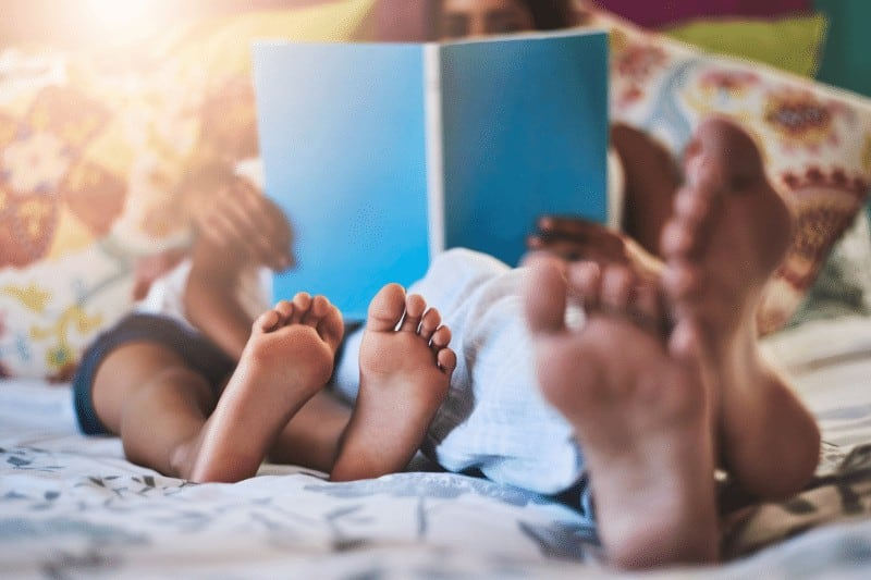 woman resting and reading a book to her children | 4 tips to help busy moms be more like Jesus