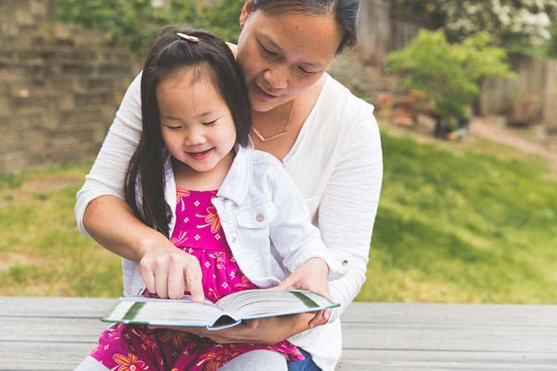Christian mom reading the Bible to her daughter | A Realistic Family Devotional Strategy