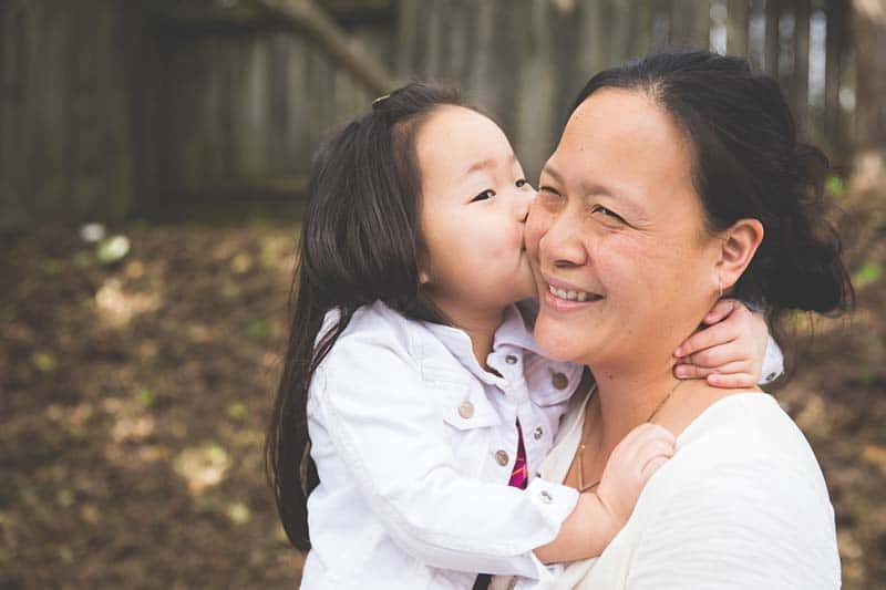 young child kissing her mother's cheek | A Realistic Family Devotional Strategy
