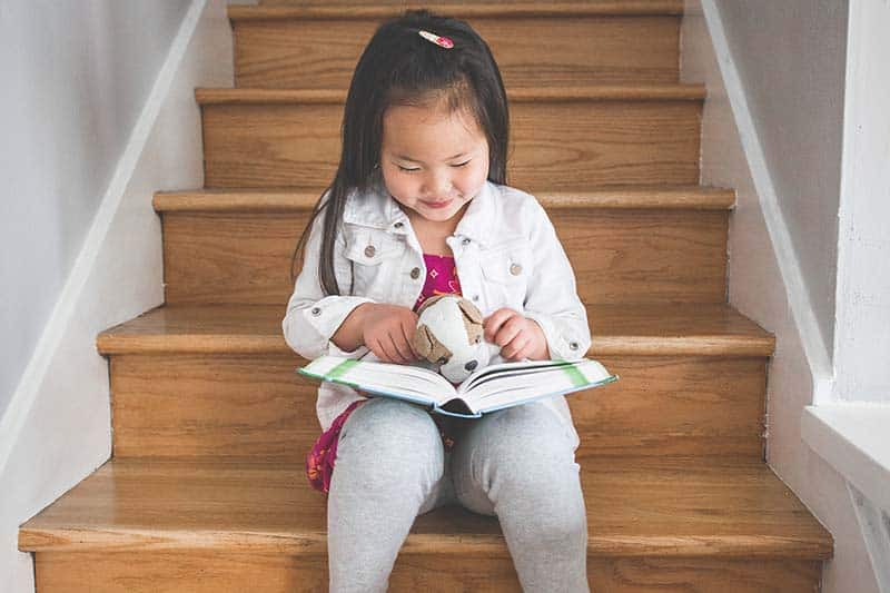 Young girl reading the Bible to a stuffed animal | A Realistic Family Devotional Strategy