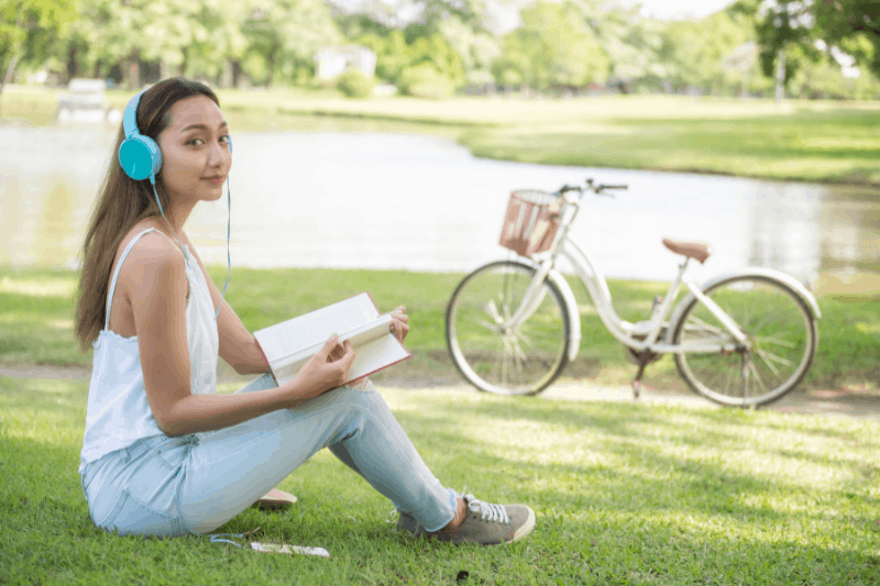 young woman sitting in the park with her bike working on her free summer Bible study from Living by Design Ministries