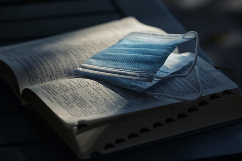 Picture of an open Bible with a folded mask atop it   How to Re-Engage in Church Life Post-Pandemic