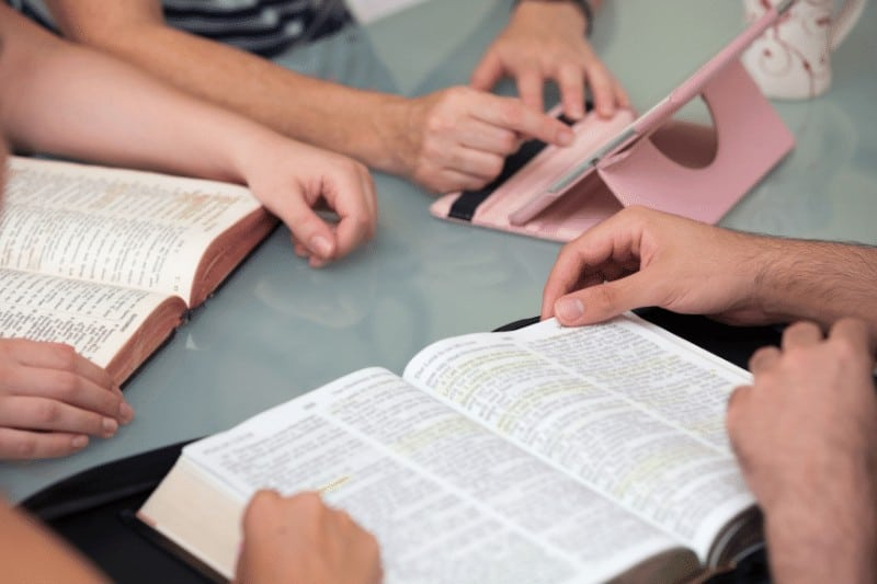 picture of friends gathered around a table with open Bibles and hands   How to Re-Engage in Church Life Post-Pandemic