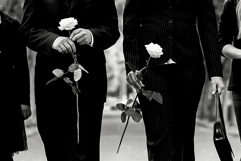 people at a funeral holding roses | A Broken Hallelujah: Practicing Gratitude in Seasons of Grief