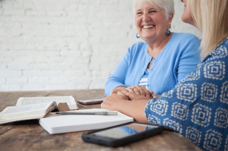 Two older Christian women studying their Bibles and laughing together.