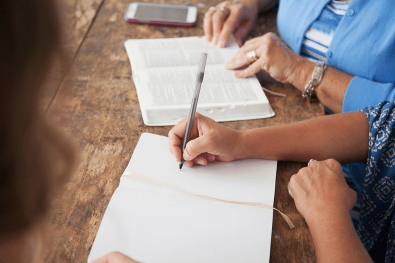 woman's hand writing notes alongside an open Bible turned to the book of Galatians