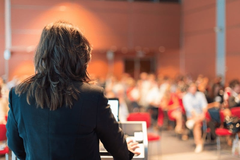 Ambitious Christian woman speaking in front of a crowded room of people.