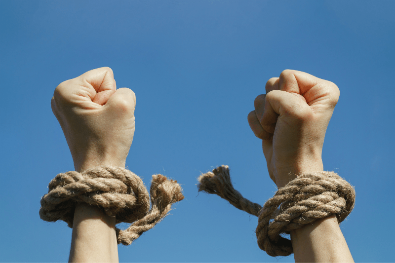 color photo of two fists with rope ties around wrists broken to represent freedom from condemnation in Christ