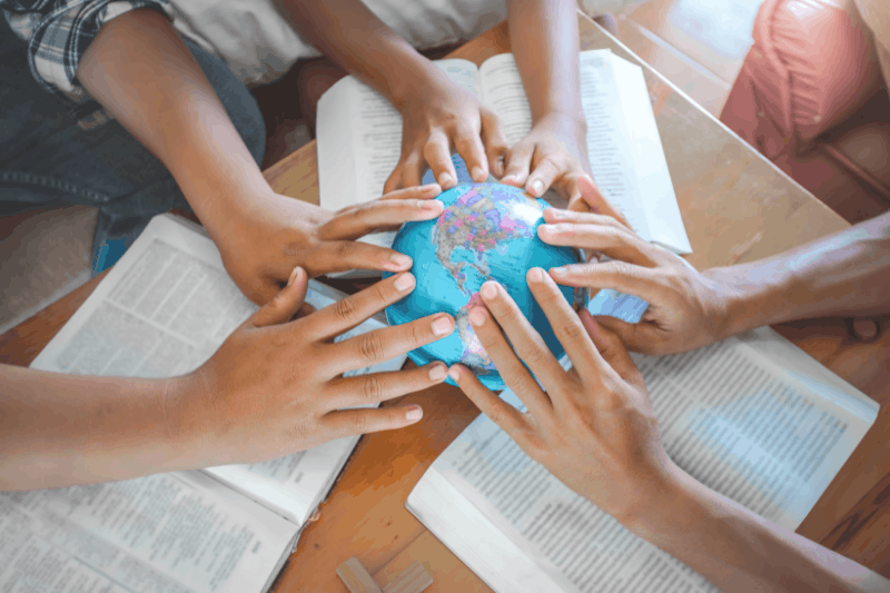family sitting around a table with Bibles and hands on a globe  - visual representation of a biblical worldview