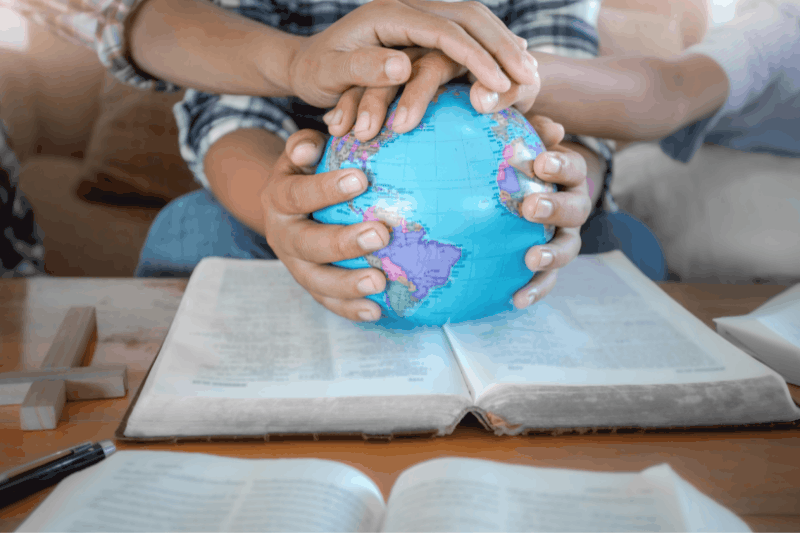 Christian family with hands on a globe sitting on top of the Bible - visual representation of a biblical worldview