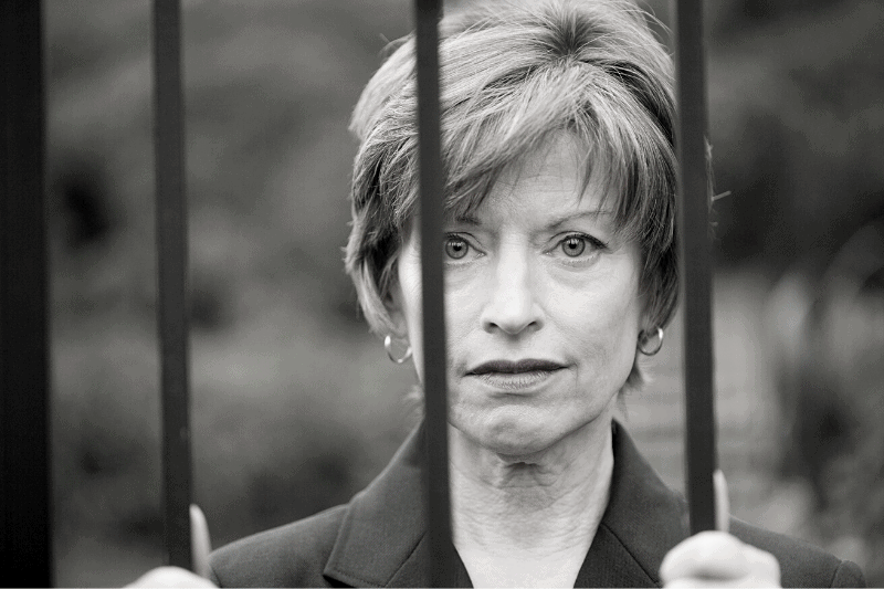 black and white image of a sad woman looking out from behind bars
